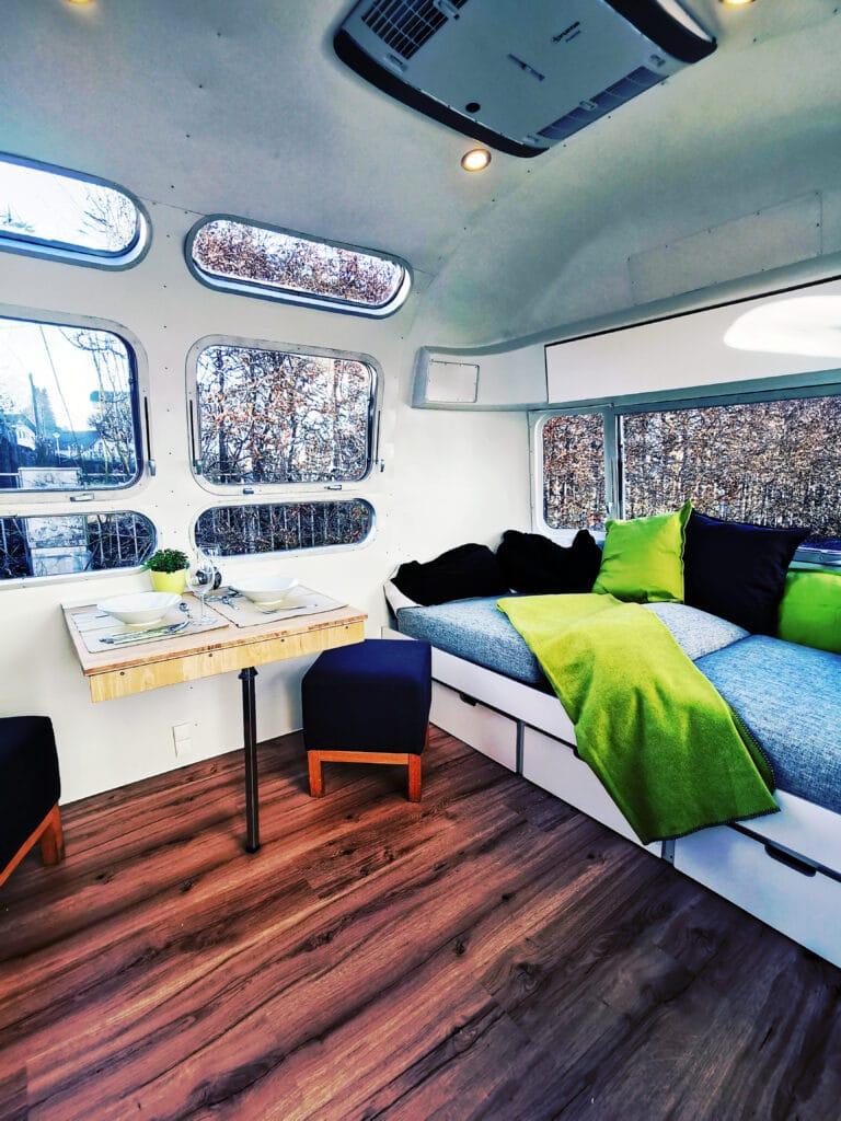 Airstream Living Tiny Home Kaufen Verkauf Wohnwagen Sitzecke Couch Tisch Fenster 1